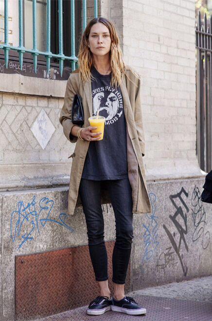 Comprar ropa de este look: https://lookastic.es/moda-mujer/looks/gabardina-camiseta-con-cuello-barco-vaqueros-pitillo-zapatillas-bajas-cartera-sobre/5899   — Tenis Negros  — Vaqueros Pitillo Negros  — Camiseta con Cuello Circular Estampada Azul Marino  — Gabardina Marrón Claro  — Cartera Sobre de Cuero Negra