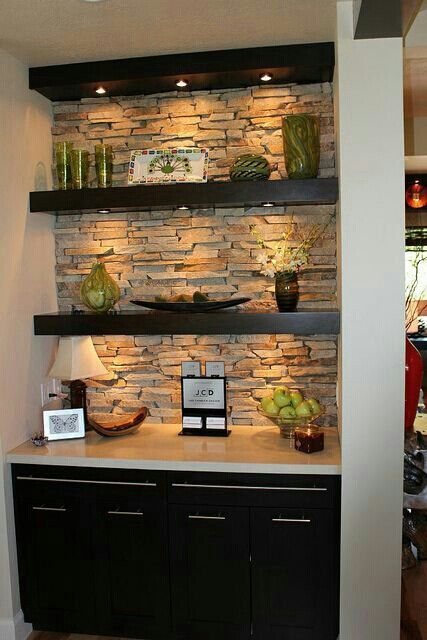 Stacked stone with warm wood.  Love the integrated puck lights underneath each wooden shelf.