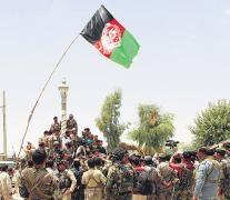Un destacamento de fuerzas de seguridad de Afganistán iza la bandera nacional en una plaza de la provincia de Nawa.