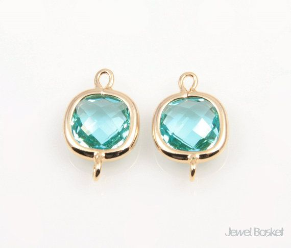 Item Details        (12,013)   Shipping & Policies These charming aquamarine color glass and gold frame connectors will be perfect for hand making jeweleries. This listing is for 2 pieces of mint connector beads. The shape is square and they have 2 nice sized holes for your own designs. They are made of brass, aquamarine color glass and are plated shiny gold.  - Highly Polished Gold Frame (Tarnish Resistant) - Aquamarine Color Glass - Brass and Glass / 9mm x 14mm - 2pcs / 1pack