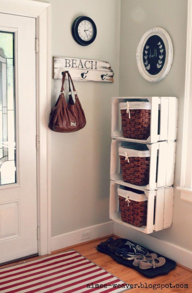 Dans l'entrée : assemblage de caisses en bois et panière en osier pour ranger les affaires en toute élégance !