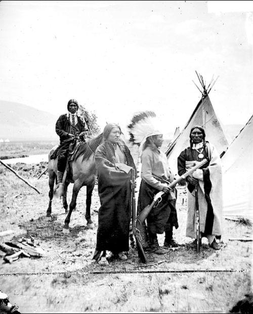 Four Ute men near tepees