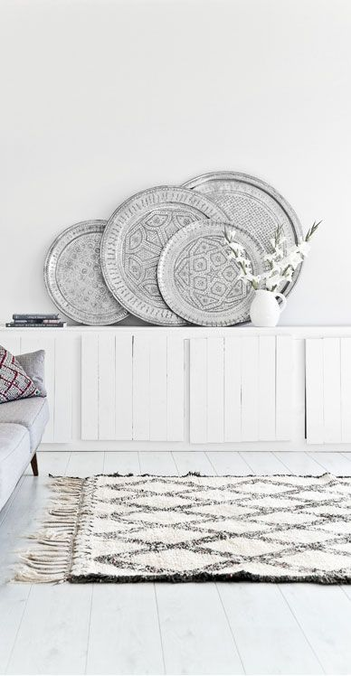 White board sideboard, stacked Moroccan metal trays and a Beni Ouarain Moroccan rug.
