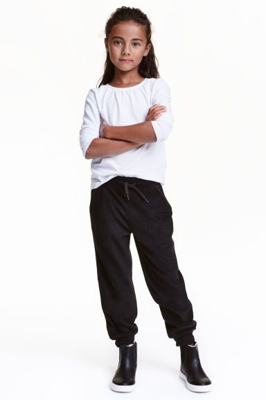 Fleece trousers: Trousers in soft, thermal fleece with an elasticated drawstring waist, side pockets and ribbed hems.