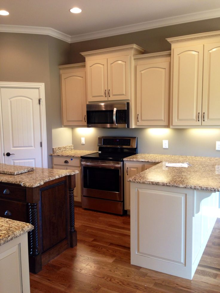 Almond Brittle Porter Paint color cabinets. Dark Walnut stain Island. St Cecelia Granite.