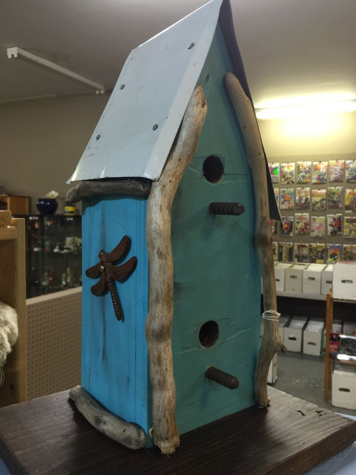 Rustic birdhouse from reclaimed wood with metal roof.