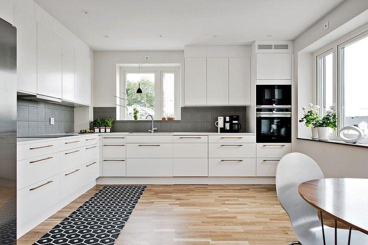 Vitt kök med köksluckan Solid och  rejäla och tåliga arbetsbänkar från Silestone. Infällda spotlights i tak. Komplett utrustat med inbyggnadsugnar, induktionshäll, fläktskåp, kyl och frys.