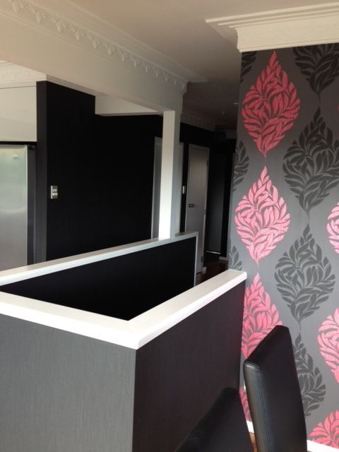 More of the Howick renovation. Adding a statement wall of patterned wallpaper to the dining area creates a separate space in an otherwise open plan area #wallpaper #black #white #kitchen #dining #leather #interiordesign #designer