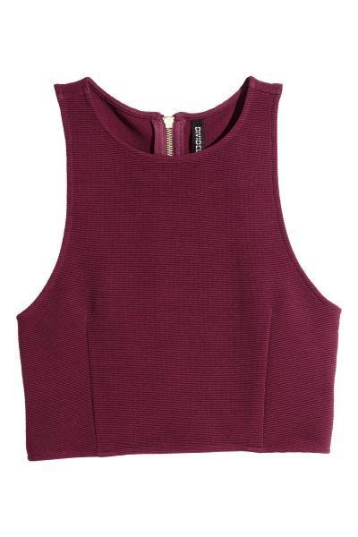 Top curto: Top curto e sem mangas em jersey canelado com secções recortadas nos lados e fecho éclair visível atrás.