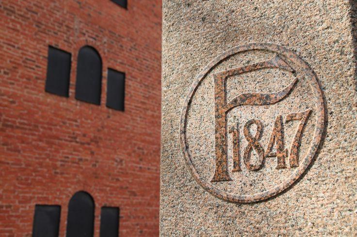 Kehräämön portinpylväissä on vuosiluku 1847, jolloin A.W. Wahren perusti Forssaan kehräämön. Taustalla puuvillamakasiini, jossa toimii nykyisin Forssan museo.