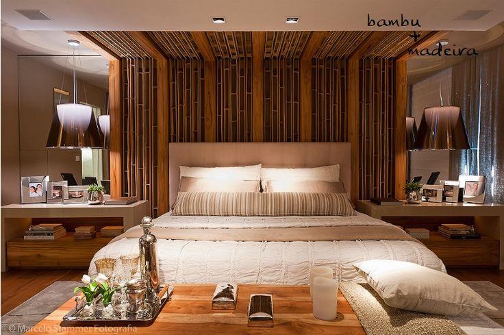 No ambiente todo clarinho, o destaque é o painel de madeira e bambu que marca a área da cama na parede e no teto. O layout é bem simétrico, com criados iguais (muito lindos, por sinal), e pendentes bem modernos, que criam um contraste com os elementos naturais.