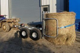 ATV bale trailer holding a round bale of hay. ATV single axle bale trailer has wraparound arms. The single bale trailer can move large round bales of hay, silage or straw with ease using an ATV, compact tractor, or four wheel drive vehicle. For info:  http://www.fresh-group.com/atv-bale-trailer.html