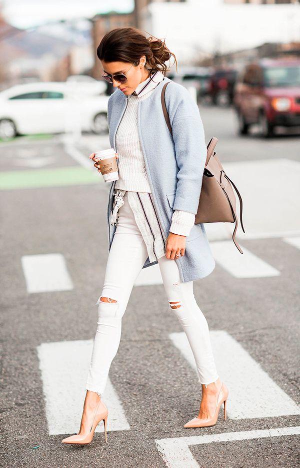 Christine Andrew atravessa a rua posando para foto de street style usando camisa com listras, sueter branco, casaco azul serenity, calça jeans branca skinny destroyed e scarpin nude