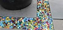 Glass pebbles in an assortment of bright colors being used to fill the gap between paving stones