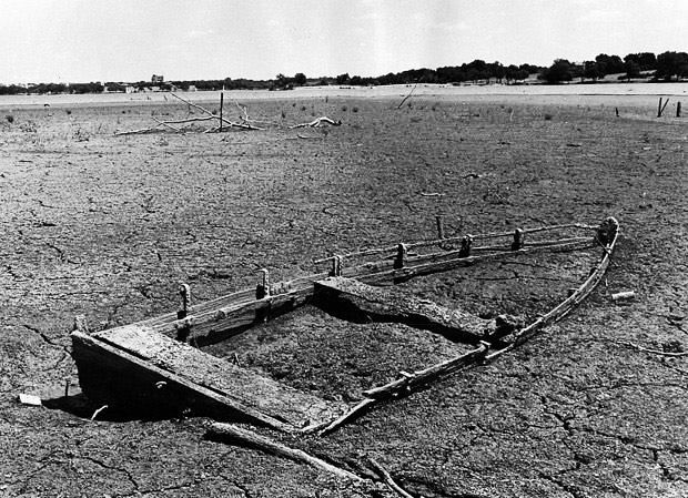 A sunken boat sits on the cracked bottom of White Rock Lake in Dallas, Texas on August 8, 1970, in this photo shot off West Lawther Drive, as a drought stretched into its 16th day in Dallas. Photo by Chris Wilkins with Dallas Morning News.