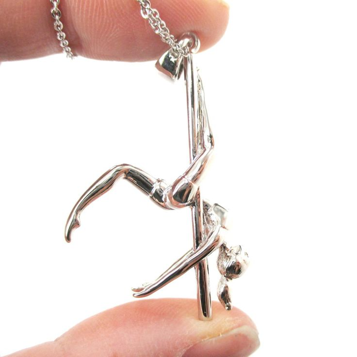- Description - Details An aerial dance inspired necklace made with a pendant in the shape of a girl doing an upside down leg hang on a pole in silver! The perfect gift for those who love this sexy sp