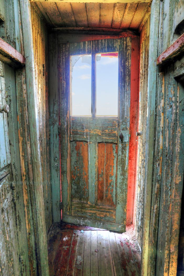 Inside the Old Caboose caboose; abaonded; prairies; old; falling in; weathered; decay; rural decay; red; peeling paint; broken windows; grassy field; blue skies; southern Saskatchewan; RM of Shamrock; old train; old caboose; decay; red paint; old door; broken door; rotten