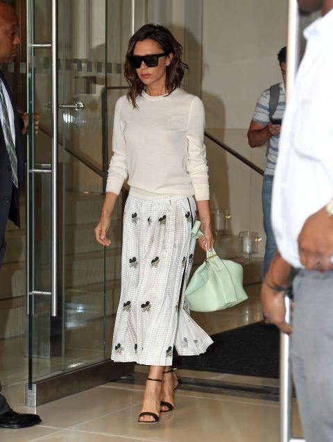 Un segundo look de Victoria Beckham esta vez en clave lady con jersey, falda estampada, sandalias al tobillo y bolso en verde menta.