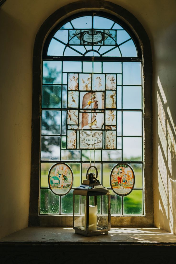 Beautiful stained glass and candle lantern inside the country church in the grounds of @wasingpark, Berkshire, UK. Photo by Benjamin Stuart Photography #weddingphotography #wasingpark #countrywedding #churchwedding #ceremonydecor #window