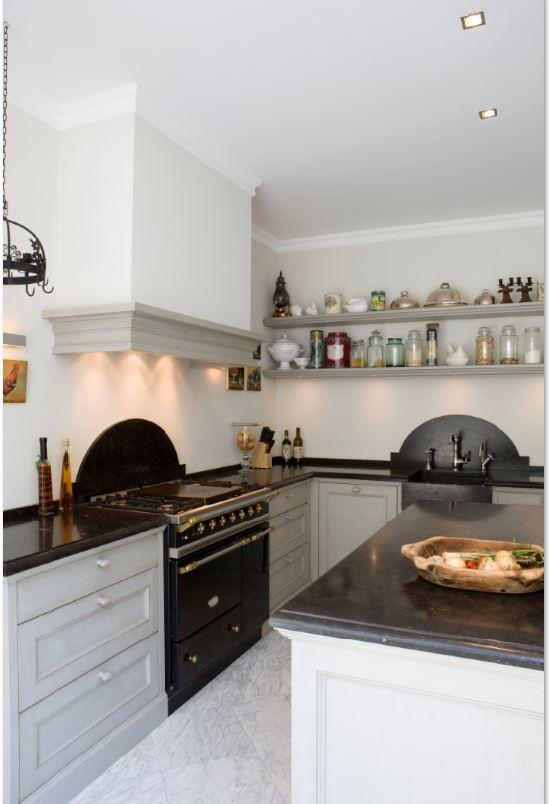 Klassieke keuken in massief 3-laags eiken. Paneelfronten met klokprofiel (klein). Eivormige houten knopjes in kleur van de keuken. Belgisch hardstenen aanrechtbladen met papegaaienbek. Achterwanden en spoelbak (uit één stuk) ook in Belgisch hardsteen. Fornuis is van Lacanche - The Living Kitchen by Paul van de Kooi