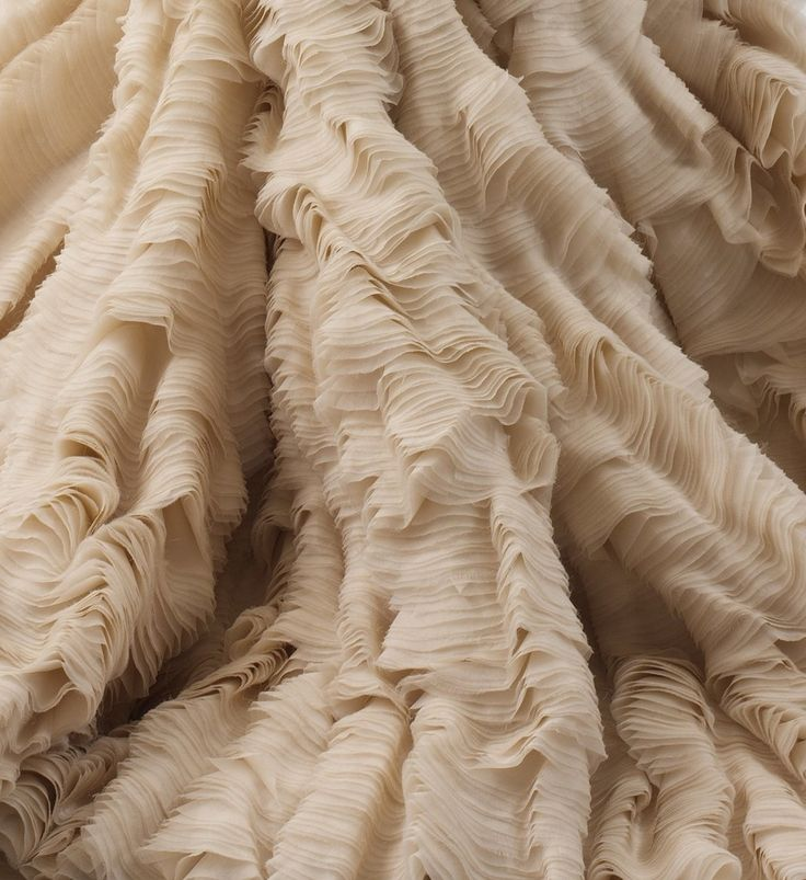 "Oyster Dress (Detail) Alexander McQueen   Spring/Summer 2003 A number of gowns in Alexander McQueen's ""Transitions"" collection of spring/summer 2003 appear to be poetic renderings of a disaster at sea. While a similar dress appeared colored like the plumage of a tropical bird, this gown of sand-colored organza recalls the mille-feuille ridging on the surface of a shell. The hem of the skirt, like the wavy lip of a giant mollusk, further emphasizes the seashell quality of the gown. But unlike…"
