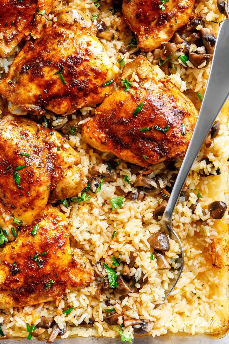 Easy Oven Baked Chicken And Rice With Garlic Butter Mushrooms mixed through is winner of a chicken dinner! Chicken thighs bake on top of buttery, garlicky, soft and tender rice with crispy edges. ALL the chicken flavours bake right in! Dinner doesn't get any easier! | cafedelites.com