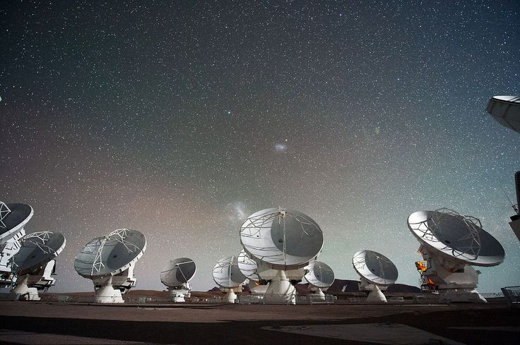 A Atacama Large Millimeter submillimeter Array (ALMA) à noite sob as nuvens de Magalhães