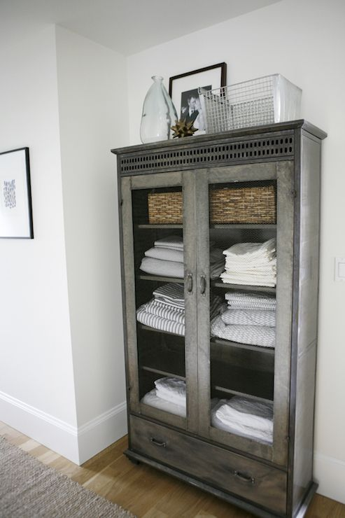 Hallway features galvanized metal linen cabinet with glass doors filled with ticking stripe sheet sets and white linen sheet sets topped with recycled glass vase and vintage wire basket alongside jute runner.