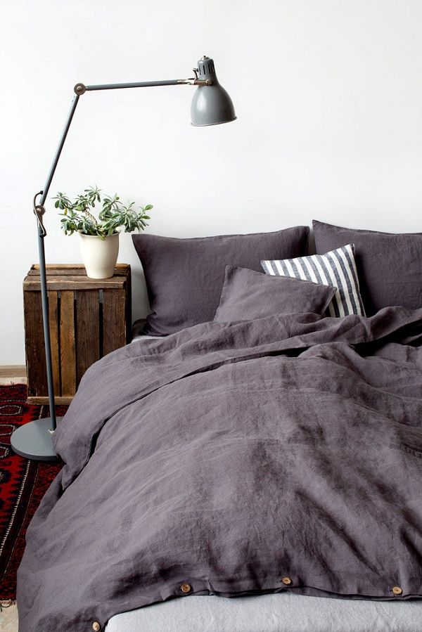 darker bedding incorporating stripes for a masculine style bedroom