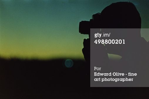 Photographer in silhouette taking photo : Foto de stock. Getty Images and Edward Olive analog stock image photo.