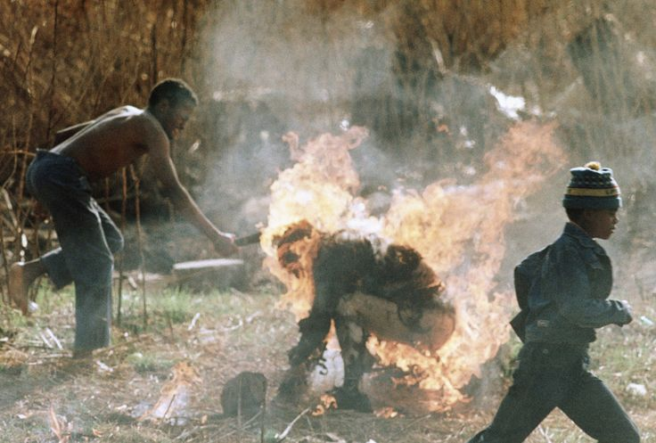 A man clubs a burning man during violence in Soweto, South Africa, between the largely Zulu group Inkatha and supporters of the African National Congress on September 15, 1990. As apartheid waned and...