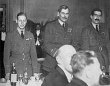 Trois hommes en uniforme militaire devant une table de restaurant où sont assis d'autres convives.
