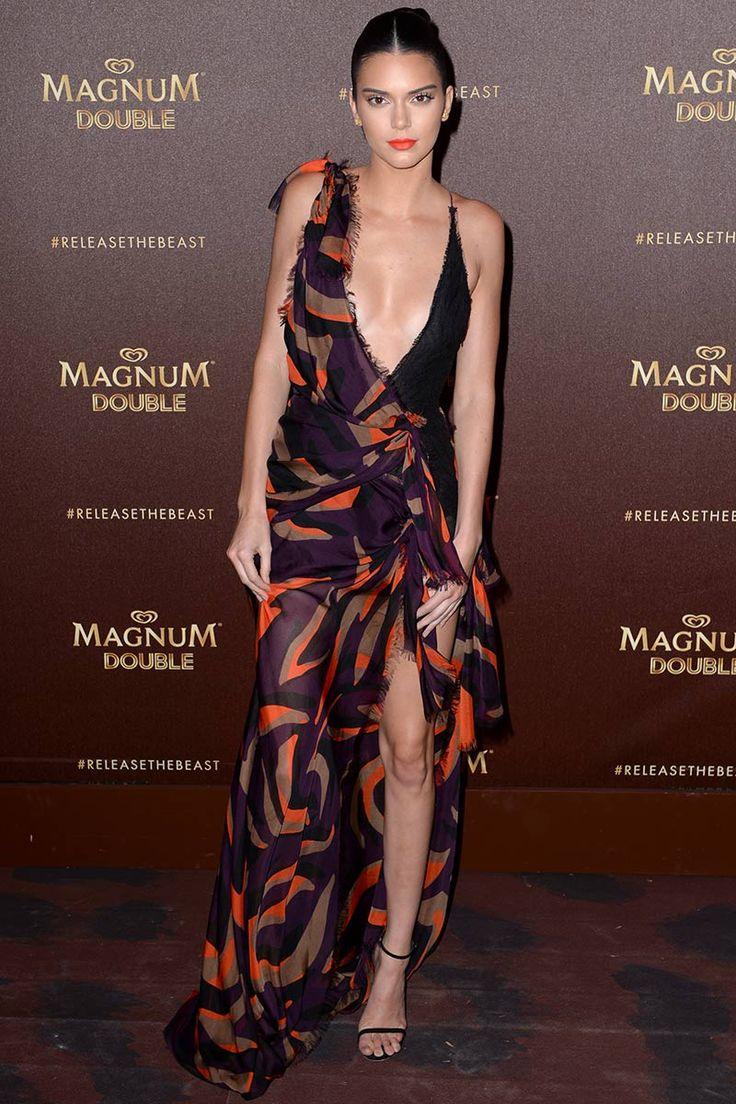 Kendall Jenner con vestido estampado de silueta asimétrica y gran escote, de Versace.
