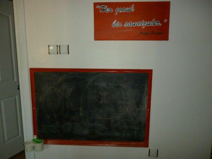 Eski bir çerçevenin arkasındaki tahta (?) siyah yağlı boya ve derz dolgusu karışımı ile boyanır. Kahverengi çerçevesi de kırmızı yapışkanlı folyo ile kaplanır.