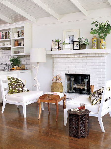 A vintage Moroccan table with modern white occasional chairs makes this fireside sitting area a cozy spot despite its light, all-white look. A collection of photographs and vases gives this shelf mantel a little extra character and plays up the laid-back cottage style in this Hot Springs, Arkansas, home.