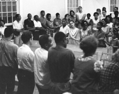 """We shall overcome, someday...  At the end of every mass-meeting we stand, link hands, and sing """"We Shall Overcome"""" while swaying gently from side to side. [Photographer unknown]"""