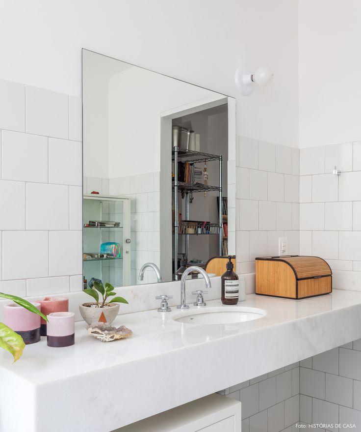 Banheiro com meia parede revestida com azulejo branco.
