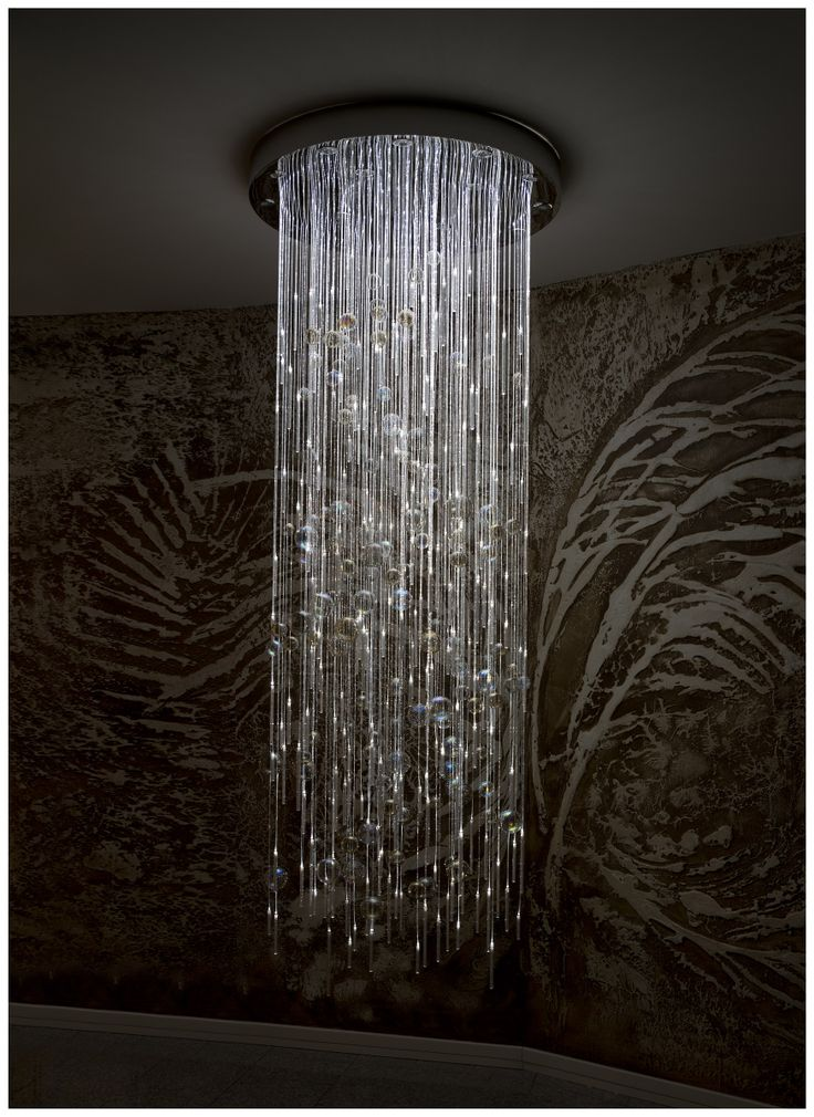 Modern chandelier made of hand blown glass and crystals hanging on sparkling fiber optics. Night mode.