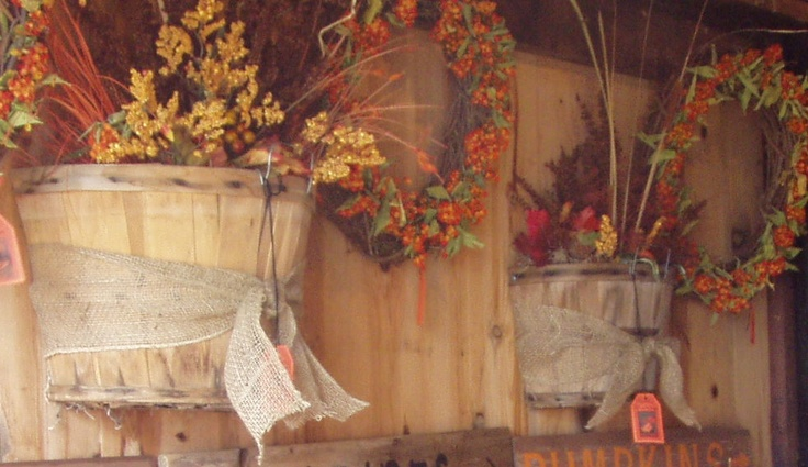 Old bushel baskets, cut in half so it can sit against or hang on a wall and filled with fall items. My friend Dori and I at it again!!!
