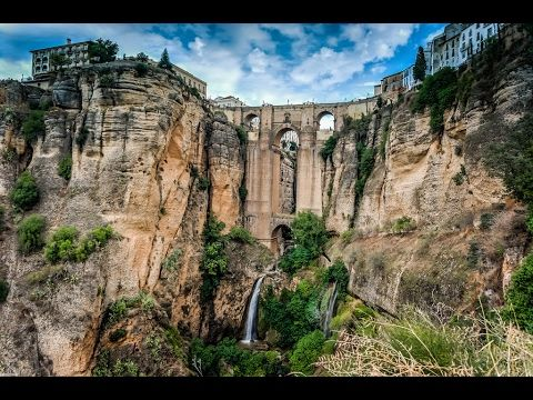 Places to see in ( Ronda - Spain ) Puente Nuevo Bridge  The Puente Nuevo is the newest and largest of three bridges that span the 120-metre-deep chasm that carries the Guadalevín River and divides the city of Ronda in southern Spain. The architect was José Martin de Aldehuela who died in Málaga in 1802. The chief builder was Juan Antonio Díaz Machuca.  The construction of Puente Nuevo Bridge was started in 1751 and took 42 years to build. Fifty workers were killed during Puente Nuevo Bridge…