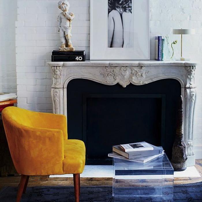 manteau de cheminée motifs baroques, chaise jaune et table transparente