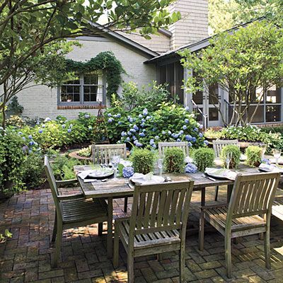 Pretty brick patio surrounded by classic blue hydrangeas