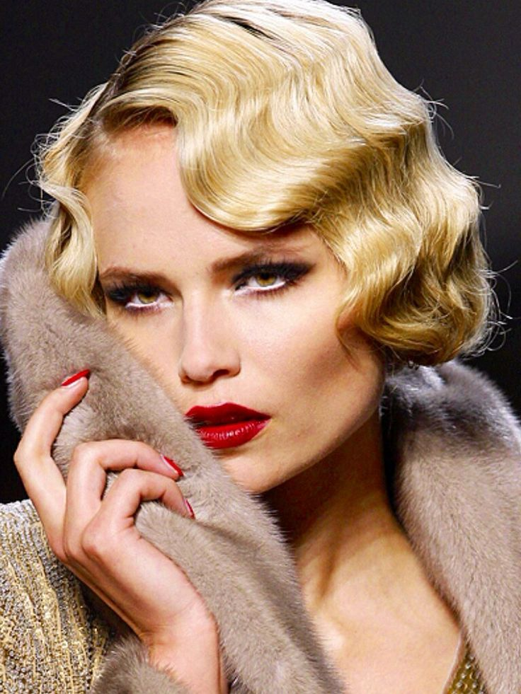 Love everything about her!  Love her finger waves in her hair and the bright fire engine red lips to the white rimmed eyes!
