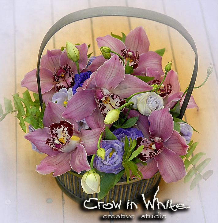Basket full of orchids with touch of lisianthus and greens. Perfect for mother day gift.