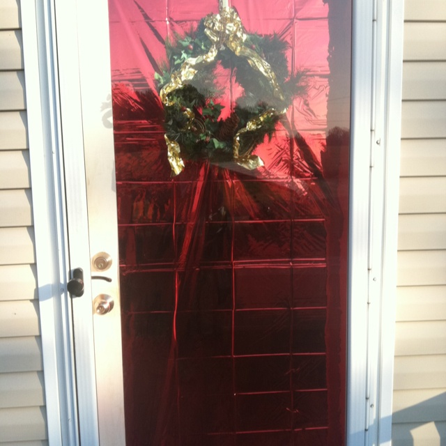 The Front Door With A Simple Red Foil Cover And Wreath