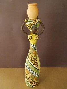 Boneca estilo Africana confeccionada com biscuit e tecidos sobre garrafas de vidro, tendo como adornos, pote de cerâmica e metais diversos. R$ 55,00