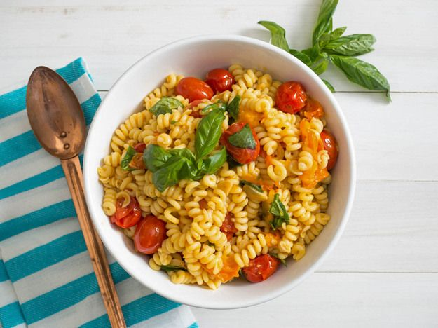 Pasta salad with raw tomatoes and basil is a common summertime dish. Here we give it a thoughtful upgrade by cooking the tomatoes just until bursting, so that they release their rich juices into a flavorful sauce that coats the pasta even when cooled. It's a new summertime must.