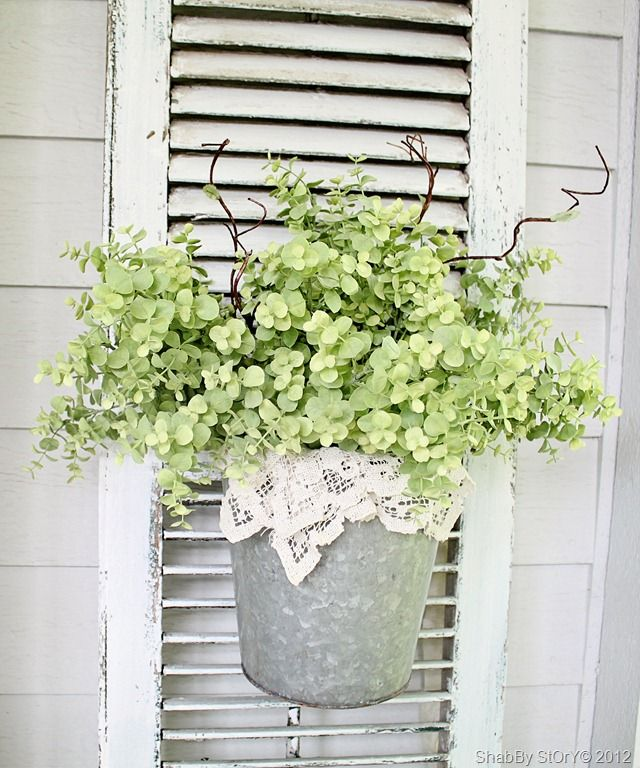 Galvanized Pot With Lace And Greenery On An Old Shutter