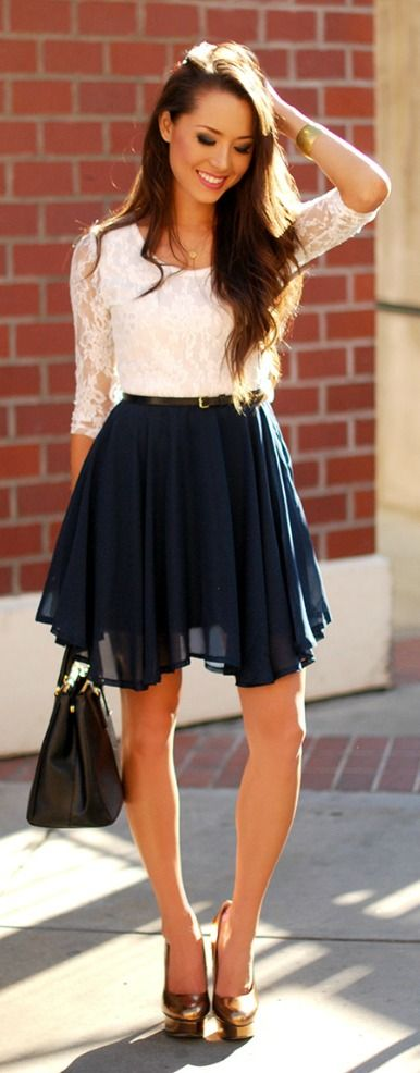 white lace top. navy blue pleated skirt,  basic black belt, black medium shoulder bag and gold accents, dainty gold necklace