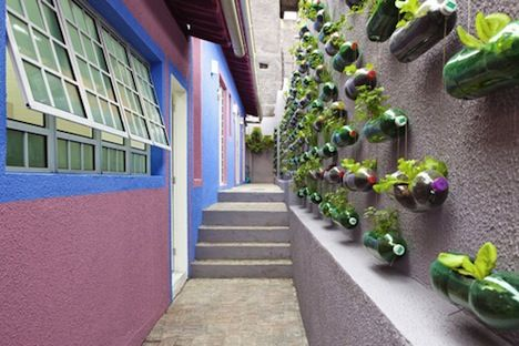 vertical garden/urban farm outside 1 bedroom house in Sao Paulo. Brazilian design studio Rosenbaum collaborates with TV show Caldeirao do Huck in a segment called Lar doce lar (Home Sweet Home), which helps families in need re-designing their homes to improve their lives and self-esteem. Those containers are plastic soda bottles! So awesome I practically can't stand it.
